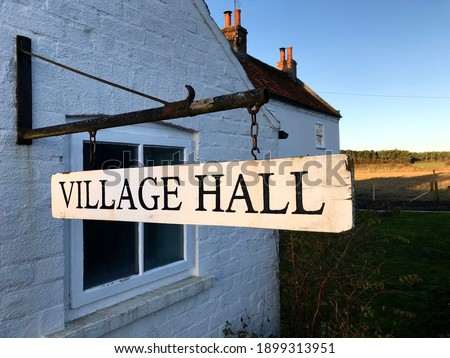 A Village Hall sign representing the community meeting place for a small English neighbourhood in the UK Royalty-Free Stock Photo #1899313951