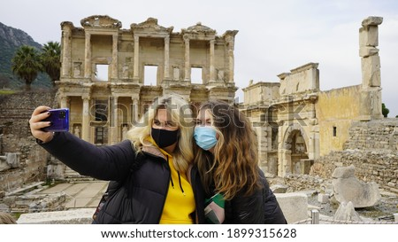 Traveling during the Covid-19 pandemic. A woman in a mask takes a selfie photo against the backdrop of attractions. Ruins of the ancient Greek city of Ephesus in Turkey. Taking pictures of himself.