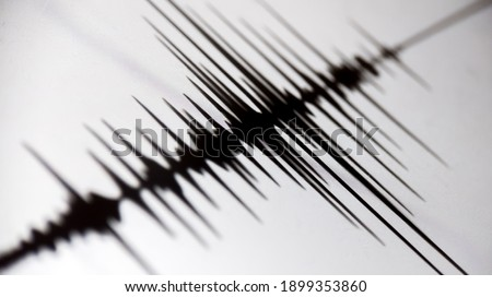 Richter scale Low and High Earthquake Waves with Vibration on white paper background, audio wave diagram concept, photo of cellphone screen, Aceh Indonesia Royalty-Free Stock Photo #1899353860