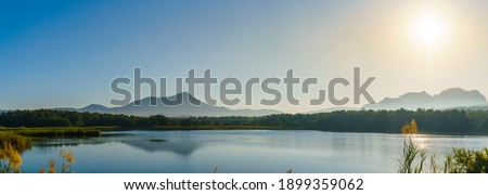 Panorama of the sunrise in the morning with mountain, lake and sky at Mae Mo, Lampang, Thailand. Royalty-Free Stock Photo #1899359062