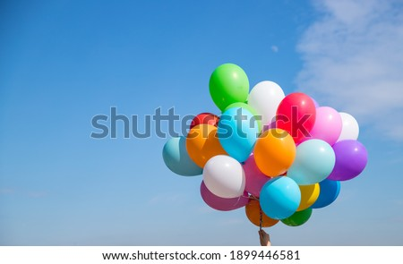 A bunch of multicolored balloons with helium on a blue sky background Royalty-Free Stock Photo #1899446581