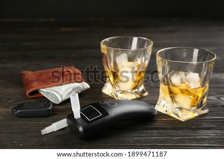 Modern breathalyzer, car key, alcohol and wallet on dark wooden background Royalty-Free Stock Photo #1899471187
