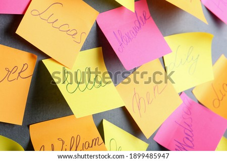 Paper notes with different baby names on grey wall Royalty-Free Stock Photo #1899485947