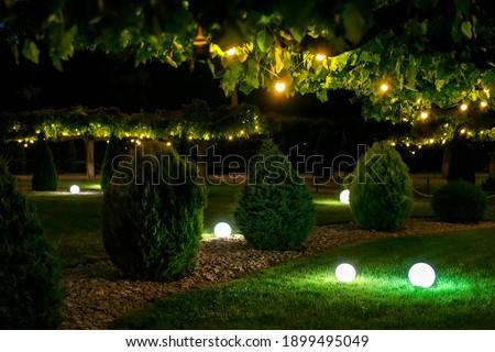 illumination backyard light garden with electric ground sphere lantern with stone mulch and thuja bush in outdoor landscaping park with garland of warm light bulbs, dark illuminate night scene nobody. Royalty-Free Stock Photo #1899495049