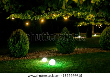 illumination backyard light garden with electric ground sphere lantern with stone mulch and thuja bush in outdoor landscaping park with garland of warm light bulbs, dark illuminate night scene nobody. Royalty-Free Stock Photo #1899499915