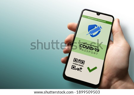 Vaccination passport for COVID-19 displayed on smartphone held in male's hand with copy space. Vaccination, disease immunity passport, health and surveillance concepts Royalty-Free Stock Photo #1899509503