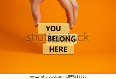 You belong here symbol. Wooden blocks with words 'You belong here' on beautiful orange background. Male hand. Diversity, business, inclusion and belonging concept.