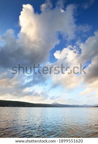 Rocky lake shores under the colorful evening sky after the rain. Dramatic cloudscape. Gare Loch, Rhu, Scotland, UK Royalty-Free Stock Photo #1899551620
