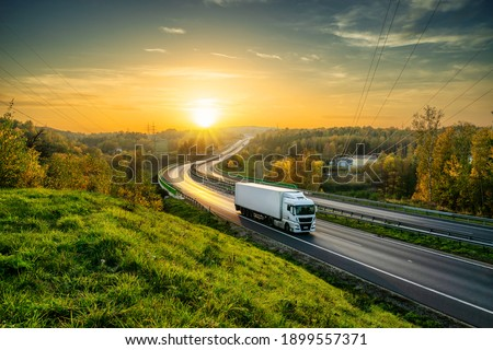 White truck driving on the highway winding through forested landscape in autumn colors at sunset Royalty-Free Stock Photo #1899557371