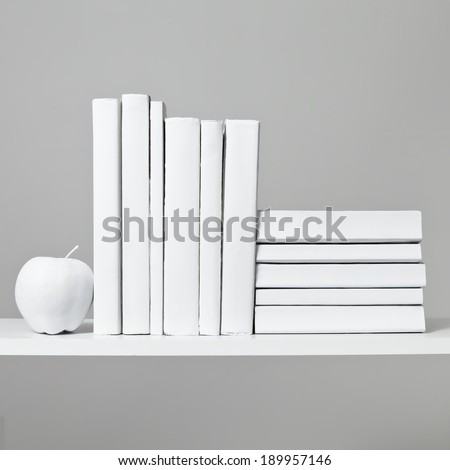 An arrangement of all white books sit on a white shelf with a white apple against a light grey background. #189957146