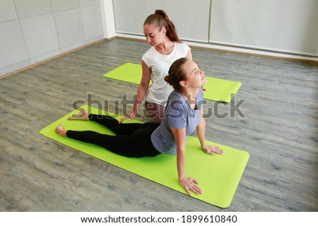 Image picture yoga coach helps beginner to make stretching exercises. Teacher assists to make position pose. Healthy lifestyle in fitness class. sporty people practicing in studio, working out indoor.