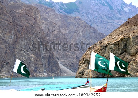 Beautiful view of Attabad lake with huge steep mountains in the background and boat in clean blue water with large Pakistani flags in Hunza, Gilgit Baltistan