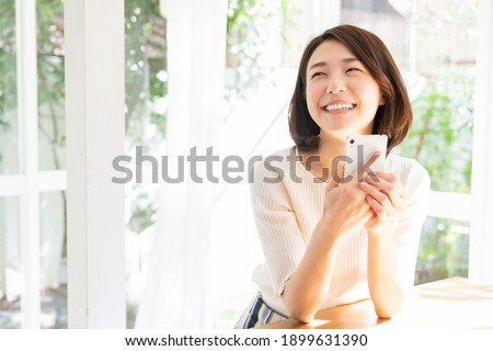 young attractive asian woman to see a smart phone, Royalty-Free Stock Photo #1899631390