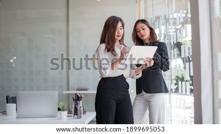 Two asian business woman work together to get the job done at the office. Royalty-Free Stock Photo #1899695053