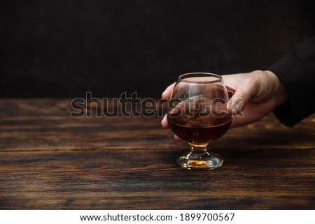 glass of alcoholic drink, hold cognac in hands on a dark background Royalty-Free Stock Photo #1899700567