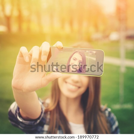 Beautiful young woman photographing herself with phone. Cute smiling young Caucasian teenage girl taking a selfie outdoors on sunny summer day.