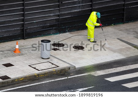 Sweeper Worker cleaning a street sidewalk with high pressure water jet machine on rainy day. Copy space Royalty-Free Stock Photo #1899819196