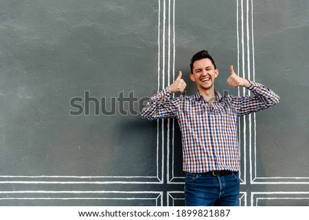happy man of European appearance shows his thumbs up and laughs. Portrait of a smiling man on a gray background. thumbs up stock photo. High quality photo