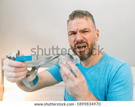 Unhappy shocked man with chronic breathing issues surprised by using  CPAP machine sitting on the bed in bedroom. Healthcare, CPAP, Obstructive sleep apnea therapy, snoring concept Royalty-Free Stock Photo #1899834970