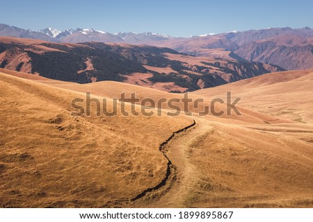 Sweeping vista landscape of the Assy Plateau, a large mountain steppe valley and summer pasture 100km from Almaty, Kazakhstan. Royalty-Free Stock Photo #1899895867