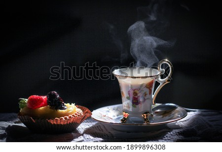 Still life with an old, vintage cup from which steam comes out, which look like a bird, cake with berries, sitting on the table. Surrounded by a dark background Royalty-Free Stock Photo #1899896308