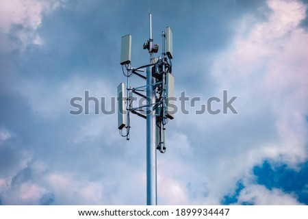 Telecommunication tower with 4G, 5G transmitters.Station with transmitter antennas on a telecommunication tower on against the background of a stormy sky. Radio emission and harm to health concept Royalty-Free Stock Photo #1899934447