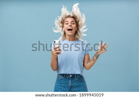 Expressing happiness with help of great tunes. Joyful amused and happy good-looking young female student jumping having fun listenign music in wireless earbuds, holding smartphone over blue wall Royalty-Free Stock Photo #1899945019