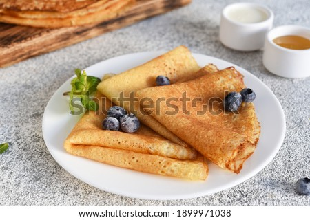 Thin pancakes for breakfast on a light concrete background. Royalty-Free Stock Photo #1899971038