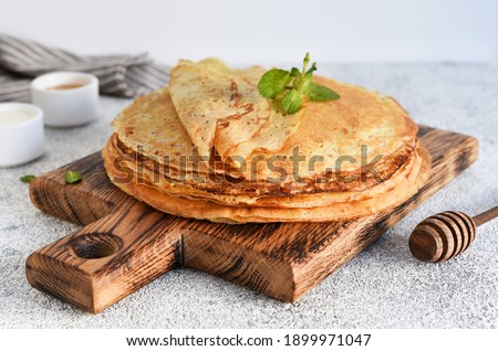 A stack of thin pancakes with sour cream and honey on a wooden board on a concrete background. Royalty-Free Stock Photo #1899971047