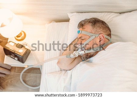 Sleeping man with chronic breathing issues considers using CPAP machine in bed. Healthcare, Obstructive sleep apnea therapy, CPAP, snoring concept Royalty-Free Stock Photo #1899973723