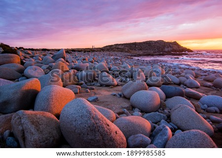 Beautiful bright colored clear water ocean during sunrise with a calm and colored sky with a rough rocky beach. Cala di Volpe, Sardinia, Italy Royalty-Free Stock Photo #1899985585