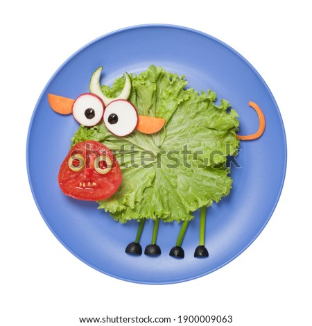 Edible bull made of vegetables. Funny food. Creative cooking idea for kids. Play with food. Isolated on blue plate on white background.