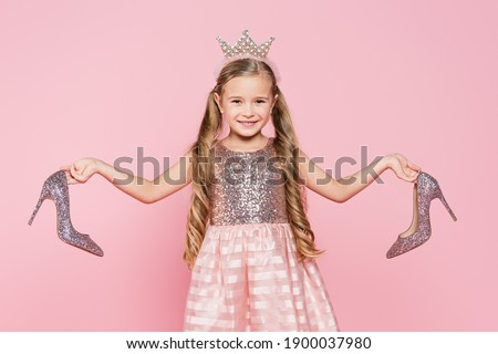 cheerful little girl in crown and dress holding heels isolated on pink Royalty-Free Stock Photo #1900037980
