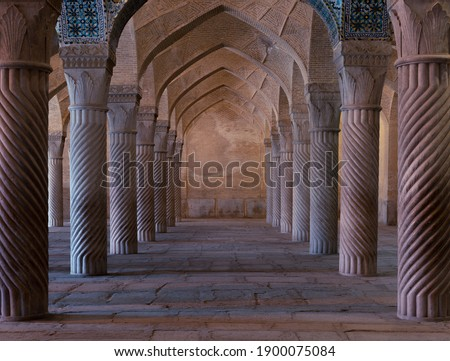 Symmetrical spiral columns in a hall of  Vakil mosque in Shiraz, Iran. Royalty-Free Stock Photo #1900075084