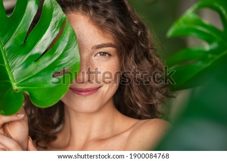 Close up face of beautiful young woman covering her face by green monstera leaf while looking at camera. Portrait of beauty woman with natural makeup and freckles standing behind big green leaves. Royalty-Free Stock Photo #1900084768