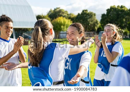 Young woman football players hugging with open arms after goal. College teammates hugging and celebrating victory. Two happy friends hugging on soccer field after sport match. Royalty-Free Stock Photo #1900084783
