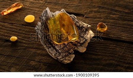A transparent bright yellow Baltic amber stone lies on a birch bark on a natural dark weathered wooden surface. Ancient amber is healing, protection, powers, magic, good  luck charm.  Royalty-Free Stock Photo #1900109395