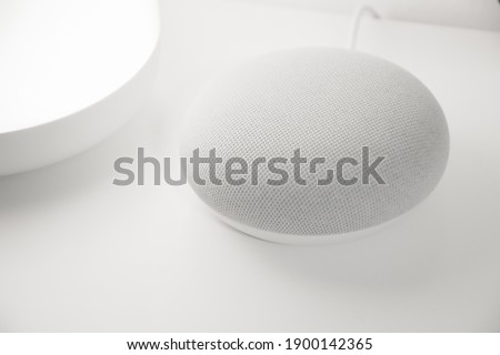 Chalk colored smart home voice assistant with a white backdrop. Smart home lamp at its side. Royalty-Free Stock Photo #1900142365