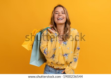 beautiful attractive smiling woman in yellow shirt and jeans holding shopping bags posing on yellow background isolated Royalty-Free Stock Photo #1900236544