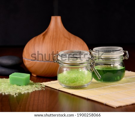 Spa and wellness setting with wooden humidifier and with green cosmetics stock images. Spa still life images. Wooden aroma humidifier, green bath salt, soap and cup with cosmetics stock images
