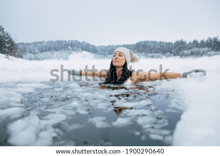 Winter swimming. Woman in frozen lake ice hole. Swimmers wellness in icy water. How to swim in cold water. Beautiful young female in zen meditation. Gray hat and gloves swimming clothes. Nature lake Royalty-Free Stock Photo #1900290640