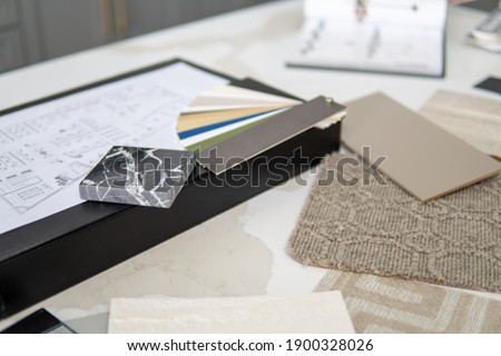 Interior designer's working table, an architectural plan of the house, a color palette, furniture and fabric samples. Drawings and plans for house decoration. Royalty-Free Stock Photo #1900328026