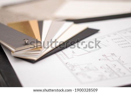 Interior designer's working table, an architectural plan of the house, a color palette, furniture and fabric samples. Drawings and plans for house decoration. Royalty-Free Stock Photo #1900328509