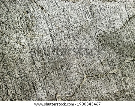 Gray grainy texture with cracks. Stock photo of rough cured cement. Solid stone background.