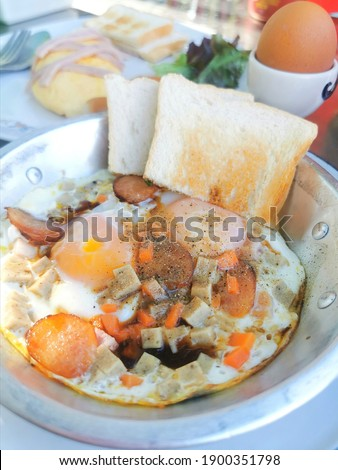 Indochina pan-fried eggsis  fried egg topping with bacon and chinese sausage in hot pan, very famous in north eastern Thailand and Vietnam.  Royalty-Free Stock Photo #1900351798