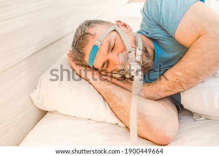 Sleeping man with chronic breathing issues considers using CPAP machine in bed. Healthcare, Obstructive sleep apnea therapy, CPAP, snoring concept Royalty-Free Stock Photo #1900449664