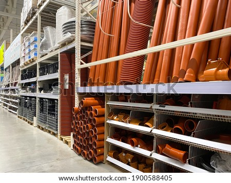 Assortment of a hardware store, pipes. Building materials and manufactured goods are stacked and put up for sale in a hardware store Royalty-Free Stock Photo #1900588405
