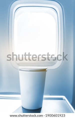 Aircraft cabin windows and paper cups