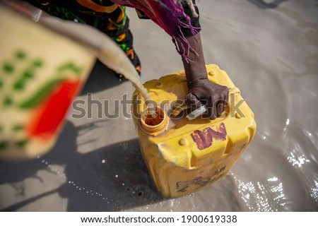 Chad woman are taking dirty water for a drink and use for daily life Royalty-Free Stock Photo #1900619338