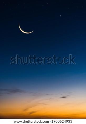 Crescent Moon on Twilight Sky in Evening Vertical with colorful sunlight after sundown,symbol Islamic Religion Ramadan, Dusk sky space background well for Arabic text present Eid al Adha, Eid al fitr. Royalty-Free Stock Photo #1900624933